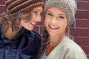 Две шапки с помпонами: полосатая и однотонная связанные спицами для женщин